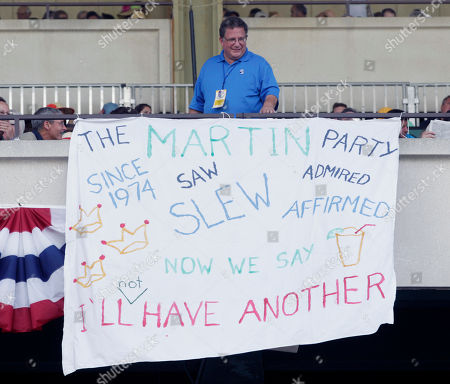 Todd Martin Todd Martin of Canton, Mich., stands behind a banner he draped at Belmont Park in Elmont, N.Y., on . I'll Have Another's bid for a Triple Crown ended with the shocking news that the colt was out of today's Belmont Stakes due to a swollen left front tendon