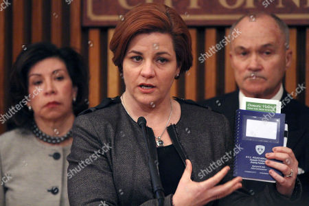 """Christine Quinn, Raymond W. Kelly, Yolanda Jimenez City Council Speaker Christine Quinn, center, is joined by Police Commissioner Raymond W. Kelly, right, and Commissioner of the Mayor's Office to Combat Domestic Violence Yolanda Jimenez as she holds up an NYPD domestic violence training manual during a news conference at Police headquarters, in New York. New York City officials are starting a new public campaign to help victims of domestic violence. Starting Tuesday, posters that say """"Report Domestic Violence. Call 911"""" will be plastered on buses and around neighborhoods where police say most domestic violence incidents occur. The posters were translated into Spanish and Russian"""
