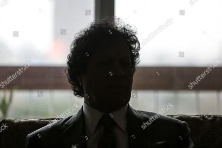 A silhouette of Ahmed Qaddaf al-Dam, cousin of Libya's former president Muammar Gaddafi, as he speaks during an interview at his apartment, in Cairo, Egypt