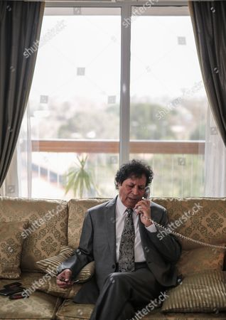 Ahmed Qaddaf al-Dam, cousin of Libya's former president Muammar Gaddafi, speaks on the phone during an interview at his apartment, in Cairo, Egypt