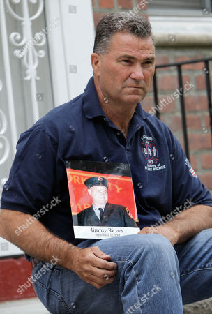 Jim Riches Retired firefighter Jim Riches poses for a picture with a photography of his son near his home in New York, . Riches, whose son was killed during the 2001 terrorist attacks on the World Trade center, will be among those to watch the arraignment of Khalid Sheikh Mohammed. The arraignment of the self-proclaimed mastermind of the Sept. 11 terror attacks and four other Guantanamo Bay prisoners will be broadcast to only six sites at four military bases in the U.S. Northeast, a Pentagon spokesman said Monday