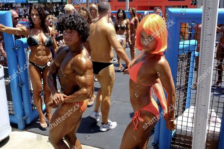 Stock Image of Contestants Bishoy Hanna, center, from Venice Beach, and Tatum Miranda, from Anchorage, Alaska, warm up prior to taking to the stage at the Muscle Beach International bodybuilding contest in the Venice Beach section of Los Angeles on . Thousands turned out to the beach on Memorial day in Southern California, marking the official start of the summer season