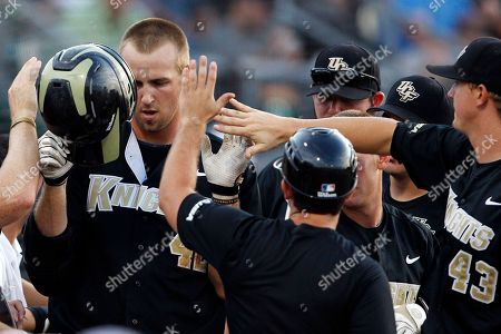 D.J. Hicks, Matt collins Central Florida's D.J. Hicks, left, is met in the dugout by Matt Collins (43) and other teammates after hitting a solo home run in the second inning during an NCAA college baseball tournament regional game against Stony Brook, in Coral Gables, Fla