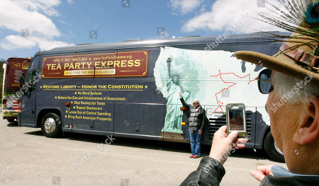 """Dan Baker, Patty Baker Patty Baker, left, strikes a pose like the Statue of Liberty for her husband Dan Baker, of Pittsburgh, to take a picture beside one of the two """"Tea Party Express"""" busses before they embark on an 11 day, 20 city tour, from Cranberry, Pa., Butler County. The political group endorsed Republican candidate Tom Smith for the U.S. Senate seat in Pennsylvania against Democrat Bob Casey Jr. during their """"Restoring the American Dream"""" national bus tour kick-off rally outside of Pittsburgh"""