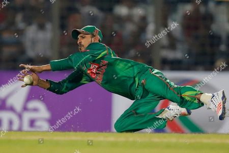 Bangladesh's Nasir Hossain dives to stop the ball as he fields against England during their third one-day international cricket match in Chittagong, Bangladesh