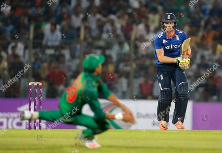 England's Sam Billings, right, watches the ball after playing a shot, as Bangladesh's Nasir Hossain, foreground, dives to stop it during their third one-day international cricket in Chittagong, Bangladesh