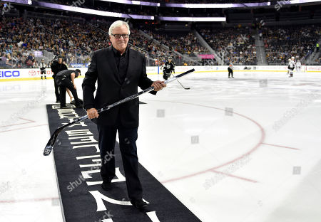 Bill Foley, owner of the Las Vegas NHL franchise, walks off the ice after accepting a silver hockey stick from Luc Robitaille, president of business operations for the Los Angeles Kings, before a preseason hockey game between the Kings and the Colorado Avalanche, in Las Vegas