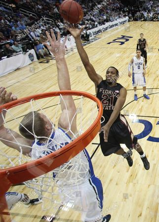 Florida State guard Michael Snaer (21) goes to the hoop as Duke forward Miles Plumlee (21) defends during the second half of an NCAA college basketball game in the semifinals of the Atlantic Coast Conference tournament, in Atlanta. Florida State won 62-59