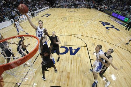 Duke forward Miles Plumlee (21) heads to the hoop as Florida State forward Okaro White (10) defends during the first half of an NCAA college basketball game in the semifinals of the Atlantic Coast Conference tournament, in Atlanta