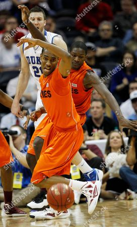 Virginia Tech guard Robert Brown (1) vies for a lose ball as teammate Dorian Finney-Smith (15) and Duke forward Miles Plumlee (21) look on during the second half of an NCAA college basketball game in the quarterfinals of the Atlantic Coast Conference tournament, in Atlanta