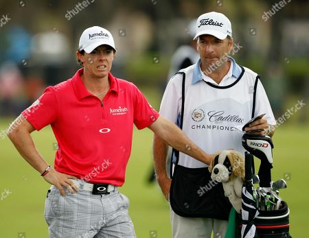 Rory McIlroy Rory McIlroy of Northern Ireland, left, and caddie J. P Fitzgerald, wait their turn on the first fairway during the third round of the Cadillac Championship golf tournament on in Doral, Fla