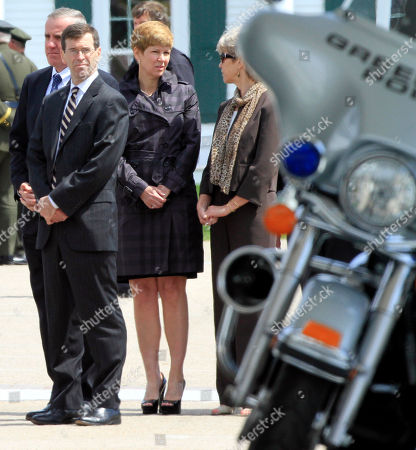 New Hampshire Attorney General Michael Delaney, left, and Senior Assistant Attorney General Jane Young, center, stand at a service for Police Chief Michael Maloney, who was shot and killed during a Drug Task Force raid. The drug raid last month in which Maloney was killed and four officers were wounded put the spotlight on a statewide drug task force that prefers to work in the dark