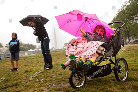 Lily James, Ellis James Ellis James, 4, of Charleston, S.C., right, reaches out to feel the rain under from an umbrella with his sister Lily James, 3, during a steady rain storm during Earth Day activities on the National Mall in Washington
