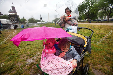 Lily James, Ellis James, Rachael James James family members of Charleston, S.C., Lily, 3, left, her brother Ellis, 4, mother Rachael James, holding Henry, 1, shelter themselves from the rain storm under umbrellas, while participating in Earth Day activities on the National Mall in Washington