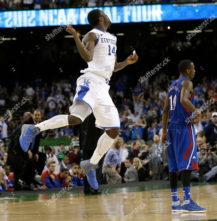 Kentucky's Michael Kidd-Gilchrist, left, celebrates in front of Kansas' Tyshawn Taylor at the end of the NCAA Final Four tournament college basketball championship game, in New Orleans. Kentucky won 67-59