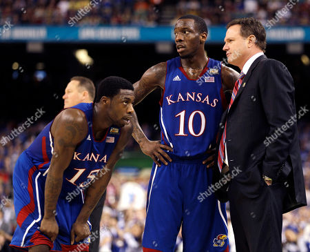 Kansas head coach Bill Self talks to guard Elijah Johnson (15) and guard Tyshawn Taylor (10) during the second half of the NCAA Final Four tournament college basketball championship game, in New Orleans