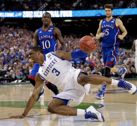 Kentucky forward Terrence Jones (3) slides on the floor as he tries to gain control in front of Kansas guard Tyshawn Taylor (10) and center Jeff Withey (5) during the first half of the NCAA Final Four tournament college basketball championship game, in New Orleans