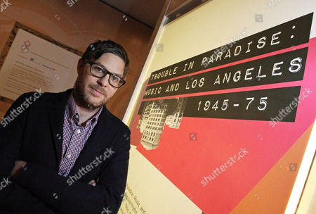 """Josh Kun This photo shows Josh Kun, professor of Communications and Journalism at the University of Southern California, posing with the exhibit he curated, """"Trouble In Paradise: Music and Los Angeles, 1945-1975,"""" at the Grammy Museum in downtown Los Angeles. The museum website says the exhibit focuses on the """"tensions between alluring myths of Southern California paradise and the realities of social struggle that characterized the years following WWII"""
