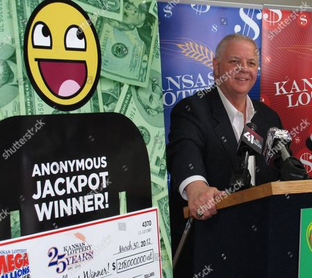 Dennis Wilson, executive director of the Kansas Lottery, shares the spotlight with a poster depicting the anonymous winner of a share of a $656 million Mega Millions jackpot during a news conference, at lottery headquarters in Topeka, Kan. The holder of a winning ticket from Kansas has come forward but doesn't want to be identified publicly