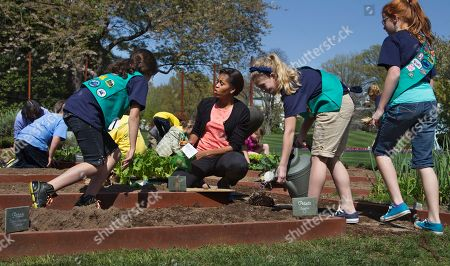 Michelle Obama, Emily Burnham, Emma Vonderlinn, Gia Muto First lady Michelle Obama, center, talks to Girl Scouts, from left, Gia Muto, Emma Vonderlinn and Emily Burnham, all from Fairport, N.Y. as they plant potatoes in the White House garden in Washington. From the beginning, Obama's kitchen garden has been an overachiever, churning out more peppers, parsley and eggplant than expected, and generating interest that _ yes, really _ crosses oceans