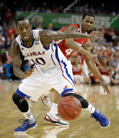 Kansas' Tyshawn Taylor steals the ball from Ohio State's William Buford, rear, during the second half of an NCAA Final Four semifinal college basketball tournament game, in New Orleans. Kansas won 64-62