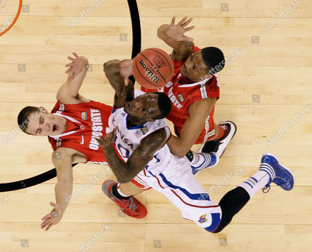 Kansas' Tyshawn Taylor, center, shoots between Ohio State's Aaron Craft, left, and Lenzelle Smith, Jr., right, during the first half of an NCAA Final Four semifinal college basketball tournament game, in New Orleans