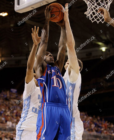 John Henson. Tyshawn Taylor, Tyler Zeller Kansas Jayhawks' Tyshawn Taylor (10) is defended by North Carolina Tar Heels' John Henson (31) and Tyler Zeller (44) during the second half of the NCAA men's college basketball tournament Midwest Regional final, in St. Louis