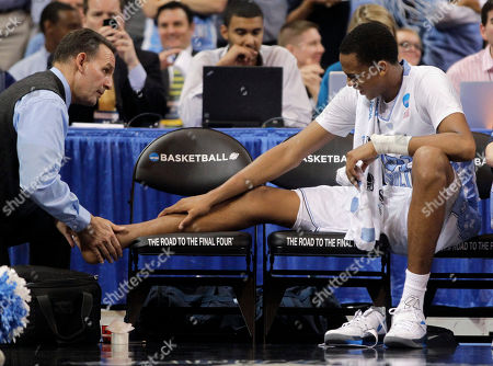 John Henson A trainer looks at North Carolina forward John Henson's ankle during the first half of the NCAA men's college basketball tournament Midwest Regional final against Kansas, in St. Louis