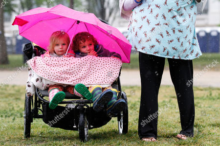 Rachael James, Lily James, Ellis James Lily James, 3, left, and her brother Ellis James, 4, of Charleston, South Carolina, take shelter from the rain under an umbrella while sitting in a stroller next to their mother Rachael James, while attending Earth Day activities on the National Mall, in Washington, on