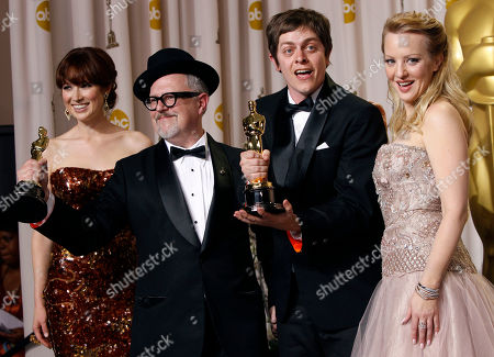 """William Joyce, second from left, and Brandon Oldenburg pose with their Oscars for best animated short film for their work in """"The Fantastic Flying Books of Mr. Morris Lessmore"""" as they stand with presenters Ellie Kemper and Wendi McLendon-Covey during the 84th Academy Awards, in the Hollywood section of Los Angeles"""