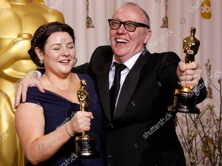 """Terry George, right, and Oorlagh George pose with their Oscars for best live action short film for their work on """"The Shore"""" during the 84th Academy Awards, in the Hollywood section of Los Angeles"""