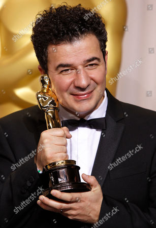 """Ludovic Bource poses with his award for best original score for """"The Artist"""" during the 84th Academy Awards, in the Hollywood section of Los Angeles"""