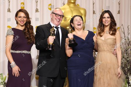 """Terry George, second from left, and Oorlagh George, second from right, pose with their Oscars for best live action short film for their work on """"The Shore"""" as they stand with presenters Maya Rudolph, left, and Kristen Wiig during the 84th Academy Awards, in the Hollywood section of Los Angeles"""