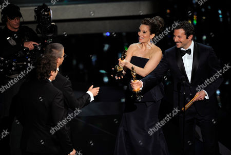 "Tina Fey and Bradley Cooper present the Oscar for best film editing for ""The Girl with the Dragon Tattoo"" to Kirk Baxter and Angus Wall during the 84th Academy Awards, in the Hollywood section of Los Angeles"