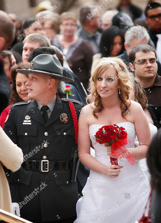 Stock Image of Ninety six couples wait in line to have their marriage certificate signed after being married during a Valentines' Day wedding ceremony outside the Arizona State Supreme Court during the 100th Anniversary celebration of Arizona's statehood, in Phoenix. Chief Justice Rebecca Birch performed the ceremony