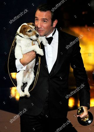 "Actor Jean Dujardin holds Uggie the dog after accepting the Oscar for best picture for ""The Artist"" during the 84th Academy Awards in the Hollywood section of Los Angeles. Uggie, the Jack Russell terrier who appeared in films like the Oscar-winning ""The Artist,"" ""The Descendants"" and ""Water for Elephants,"" has a memoir coming. Gallery Books, an imprint of Simon & Schuster, announced Friday that ""Uggie: My Story"" will come out in October. His tale of tails will be transcribed by biographer and presumed dog whisperer Wendy Holden"
