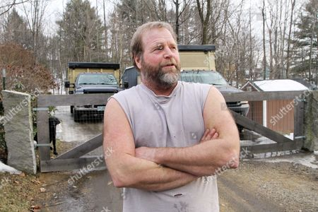 Landscaper and neighbor Jim Coffey looks across the street at the home bought by Edward Maher, under the name of Steven King in 1996, in Laconia, N.H.. The British fugitive, Maher, dubbed fast Eddie, for a 1993 armored-cart heist lived in the house with his family for several years before quickly packing up and leaving
