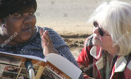 """Deloris Mack, Julie Davis In this image made from video, Alabama tornado victim Deloris Mack, left, talks with disaster relief volunteer Julie Davis of Girard, Pa., at a work project in Tuscaloosa, Ala. Davis and her husband Ken are """"disaster junkies,"""" an informal term for volunteers who make repeated trips across the United States to provide assistance after disasters"""