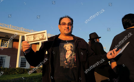 """Louis Medina Louis Medina poses with a t-shirt and pictures of Etta James as he stands in line for a public viewing for the singer, in Inglewood, Calif. James died last Friday at age 73 after battling leukemia and other ailments, including dementia. She was most famous for her classic """"At Last,"""" but over her decades-long career, she became revered for her passionate singing voice"""