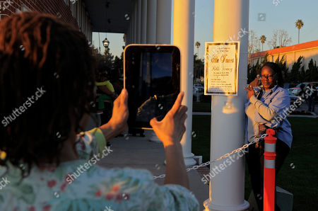 """Beverly Allen, April Bullard Beverly Allen, left, takes a pictures of April Bullard as they stand in line for a public viewing for singer Etta James, in Inglewood, Calif. James died last Friday at age 73 after battling leukemia and other ailments, including dementia. She was most famous for her classic """"At Last,"""" but over her decades-long career, she became revered for her passionate singing voice"""
