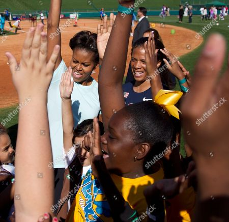 Michelle Obama, April Holmes First lady Michelle Obama celebrates after playing with kids at the ESPN Wide World of Sports Complex at the Walt Disney World Resort, in Orlando, Fla., during her three day national tour celebrating the second anniversary of Let's Move. Standing behind is paralympian April Holmes