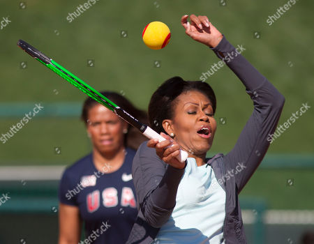 Michelle Obama, April Holmes First lady Michelle Obama misses as she plays tennis with kids at the ESPN Wide World of Sports Complex at the Walt Disney World Resort, in Orlando, Fla., during her three day national tour celebrating the second anniversary of Let's Move. Standing behind is paralympian April Holmes