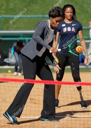 Michelle Obama, April Holmes First lady Michelle Obama plays tennis with kids at the ESPN Wide World of Sports Complex at the Walt Disney World Resort, in Orlando, Fla., during her three day national tour celebrating the second anniversary of Let's Move. Standing behind is paralympian April Holmes