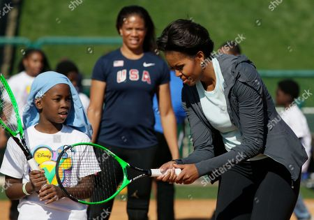 Michelle Obama, April Holmes First lady Michelle Obama shows her young tennis partner how to grip a racquet at the ESPN Wide World of Sports Complex at the Walt Disney World Resort, in Orlando, Fla., during her three day national tour celebrating the second anniversary of Let's Move. Standing behind is paralympian April Holmes