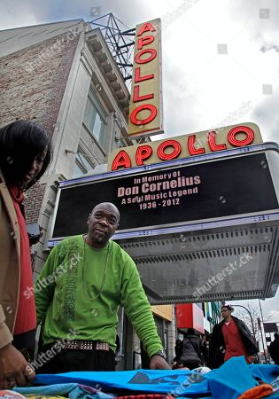 """Say'eed """"Mojo"""" Muhammad, second from left, a t-shirt designer and R&B entertainer, sells his products next to the Apollo theater while its marquee host a tribute in memory of Don Cornelius on in New York. Cornelius, the silken-voiced host of TV's """"Soul Train"""" who helped break down racial barriers and broaden the reach of black culture with funky music, groovy dance steps and cutting-edge style, died early Wednesday of an apparent suicide. He was 75. """"He was a very good person,"""" said Muhammad, who met Cornelius last year at Chicago's 40th Anniversary Soul Train Concert in his honor"""