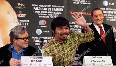 Manny Pacquiao, of the Philippines, waves as he joins his trainer Freddie Roach, left, and promoter Bob Arum, at a boxing news conference, in Beverly Hills, Calif., o promote their upcoming welterweight championship boxing match against Timothy Bradley Jr. The pair will meet at the MGM Grand Garden in Las Vegas on June 9