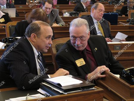 Kansas state Reps. Jerry Henry, left, a Cummings Democrat, and Tom Burroughs, right, a Kansas City Democrat, confer during a debate on a bill redrawing House members' districts, at the Statehouse in Topeka, Kan