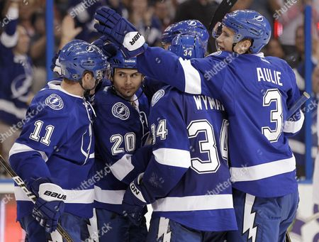 Tim Wallace, Tom Pyatt, Keith Aulie, J.T. Wyman Tampa Bay Lightning right wing Tim Wallace (20) celebrates with teammates, including left wing Tom Pyatt (11), right wing J.T. Wyman (34) and defenseman Keith Aulie (3), after scoring against the Ottawa Senators during the second period of an NHL hockey game, in Tampa, Fla
