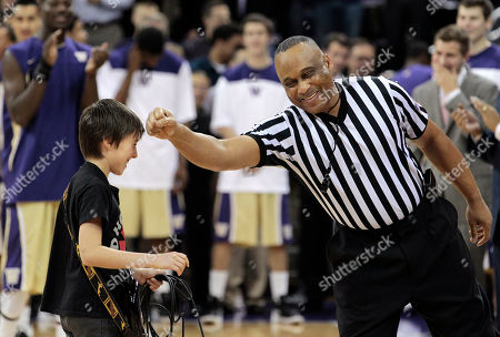 Stock Image of Bobby McRoy, Caspian Coberly Official Bobby McRoy, right, gives a playful tap to Caspian Coberly, 11, after Coberly played the national anthem on an electric guitar before Washington played UCLA in an NCAA college basketball game, in Seattle