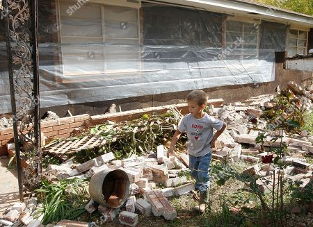 Stock Image of Logan Devereaux Five-year-old Logan Devereaux walks past some of the bricks that fell from three sides of this home in Sparks, Okla., following two earthquakes in less than 24 hours. The home owners have placed plastic around the home to try and protect what is left